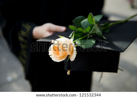 people in a gown holding a mortarboard and rose. - stock photo