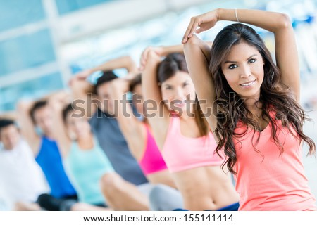 People in a gym class stretching and looking happy  - stock photo