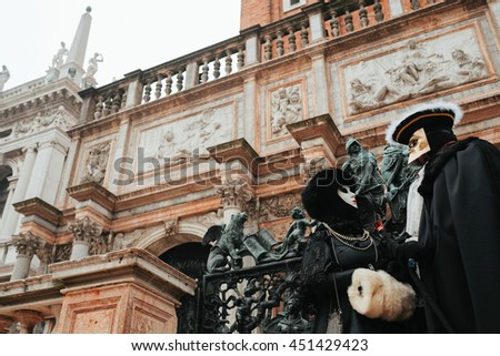People in black carnival costumes stand in the front of an old cathedral with many marble figures