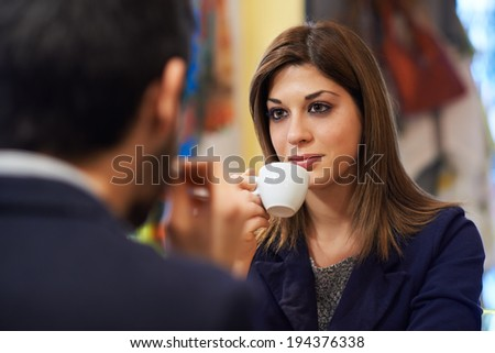 People in cafeteria with woman drinking espresso coffee and holding cup - stock photo