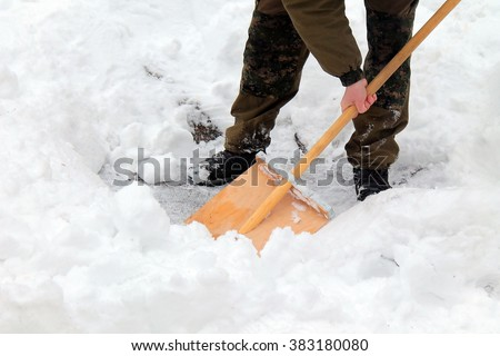 people in camoflage cleans snow shovel at winter