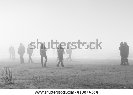 People in coats walking along foggy beach, soft focus