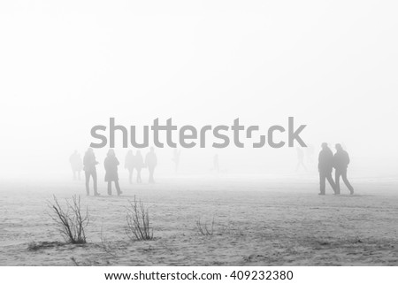 People in coats walking along the foggy beach, soft focus