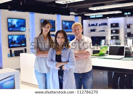 people in consumer electronics  retail store looking at latest laptop, television and photo camera to buy - stock photo