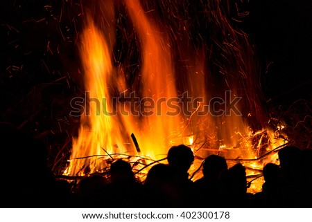 People in front of a large fire with high flames - stock photo