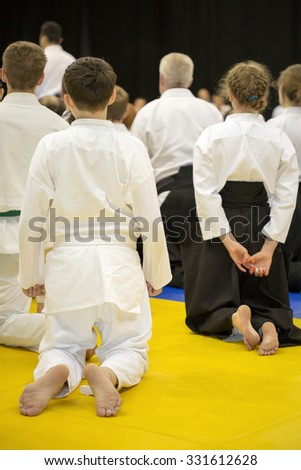 People in kimono and hakama sitting on tatami on martial arts training seminar