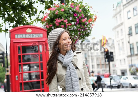 People in London- woman by red phone booth. Portrait of beautiful smiling happy young female casual professional business woman walking outside in City of Westminster, London, England, Great Britain. - stock photo