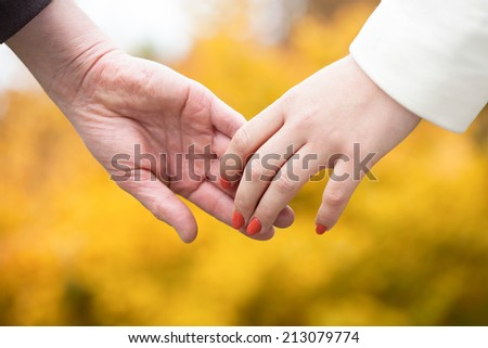 People in love holding hands in autumn park - stock photo