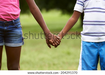 People in love with african little girl and boy holding hands in park. Cropped view - stock photo