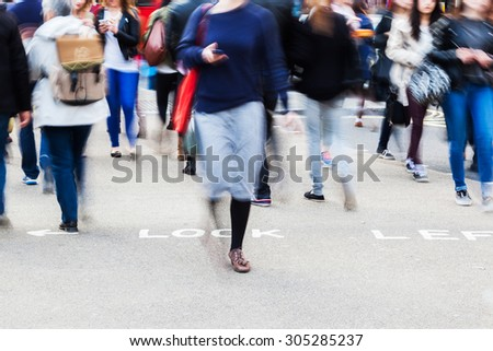 people in motion blur crossing a city street