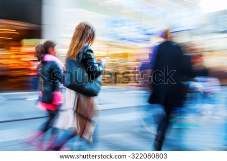 people in motion blur on the move in a shopping street of a city