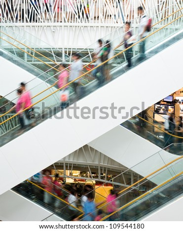 People in motion in escalators at the modern shopping mall. - stock photo