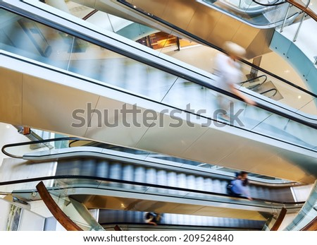 People in motion in escalators at the modern shopping mall - stock photo