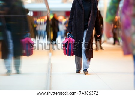 People in rush in a modern shopping mall. Close up and reflection of a woman walking - stock photo
