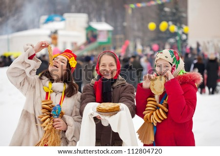 People in traditional  clothes eating pancake during  Maslenitsa festival