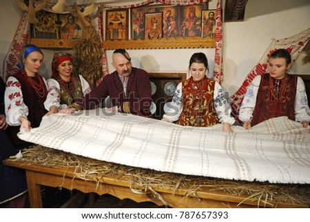People in Ukrainian native dresses standing behind table setting it with cloth to celebrate Christmas. Reconstruction of Ukrainian folk traditions for mass-media. January 4, 2018. Kiev, Ukraine