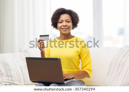 people, internet bank, online shopping, technology and e-money concept - happy african american young woman sitting on sofa with laptop computer and credit card at home - stock photo