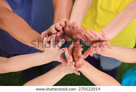 People joining their hands  on green grass . - stock photo