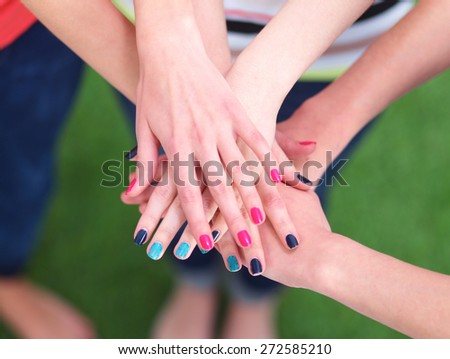 People joining their hands  on green grass - stock photo