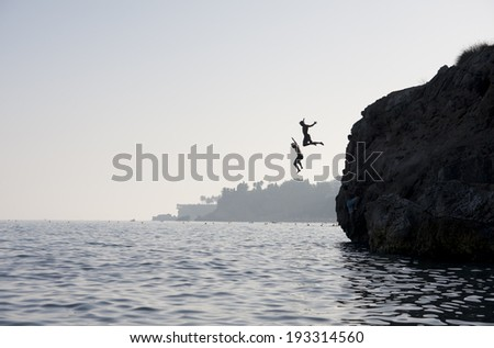 People jumping into the water from cliff - stock photo