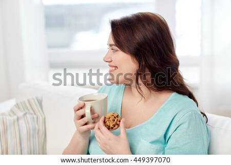 people, junk food, unhealthy eating and leisure concept - happy plus size young woman with cup of tea with cookie at home - stock photo