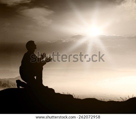 People kneeling and praying over sunset. - stock photo