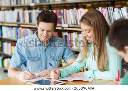 people, knowledge, education and school concept - group of happy students with tablet pc computer writing to notebooks in library - stock photo
