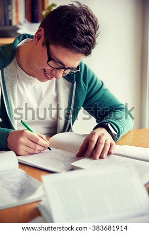 people, knowledge, education and school concept - happy student boy in glasses writing to notebook in library - stock photo