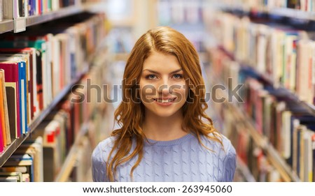 people, knowledge, education and school concept - happy student girl or young woman in library