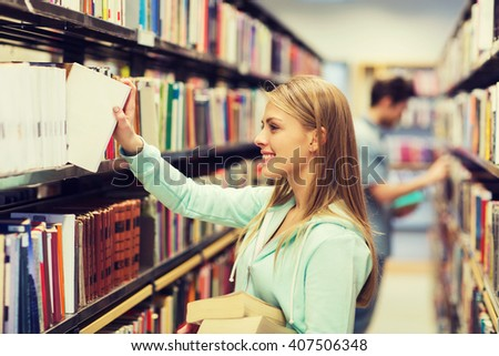 people, knowledge, education and school concept - happy student girl or young woman taking book from shelf in library - stock photo