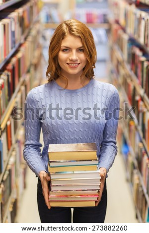 people, knowledge, education and school concept - happy student girl or young woman with stack of books in library - stock photo