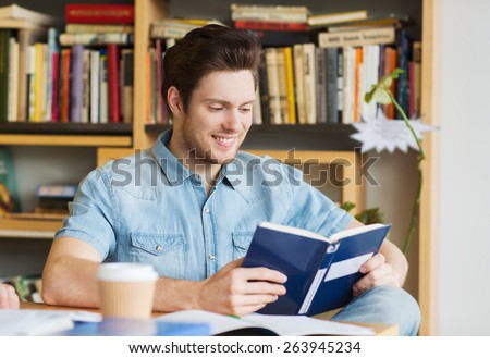 people, knowledge, education and school concept - happy student reading book and drinking coffee in library - stock photo