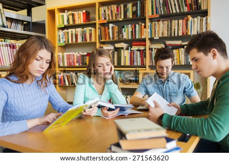 people, knowledge, education, literature and school concept - students reading books and preparing to exams in library - stock photo