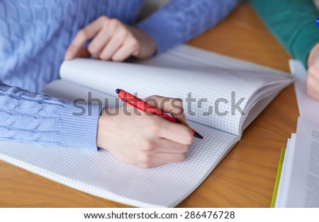people, learning, education and high school concept - close up of female student hands writing to notebook - stock photo