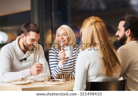 people, leisure and communication concept - happy friends meeting and drinking tea or coffee at cafe - stock photo