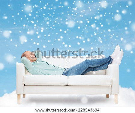 people, leisure and happiness concept - smiling man lying on sofa over blue sky with cloud and snow background - stock photo
