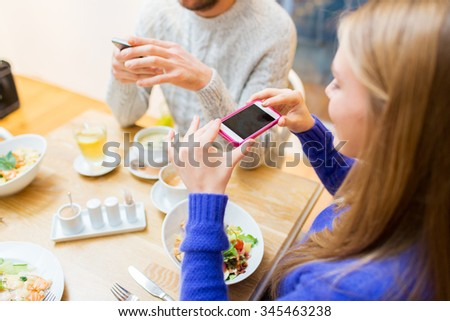 people, leisure and technology concept - close up of happy friends with smartphones taking picture of food at cafe