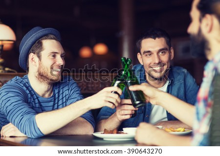 people, leisure, celebration, friendship and bachelor party concept - happy male friends drinking beer and clinking bottles at bar or pub - stock photo