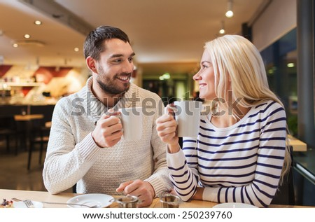 people, leisure, communication, eating and drinking concept - happy couple meeting and drinking tea or coffee at cafe - stock photo