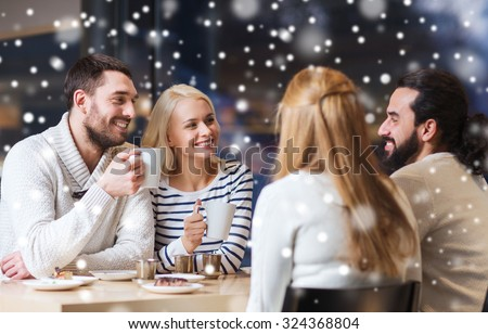 people, leisure, communication, season and concept - happy friends meeting and drinking tea or coffee at winter cafe - stock photo