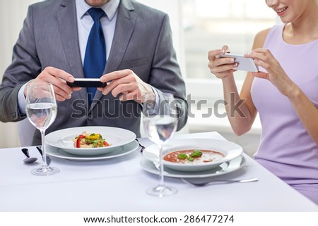 people, leisure, eating and technology concept - close up of couple with smartphones taking picture of food at restaurant