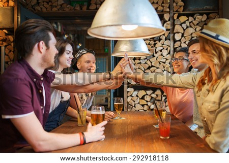 people, leisure, friendship and communication concept - group of happy smiling friends with drinks making high five gesture at bar or pub - stock photo