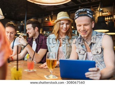 people, leisure, friendship and communication concept - group of happy smiling friends with tablet pc computer and drinks at bar or pub