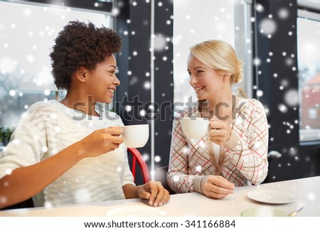 people, leisure, friendship and communication concept - happy young women meeting and drinking tea or coffee at cafe over snow effect - stock photo