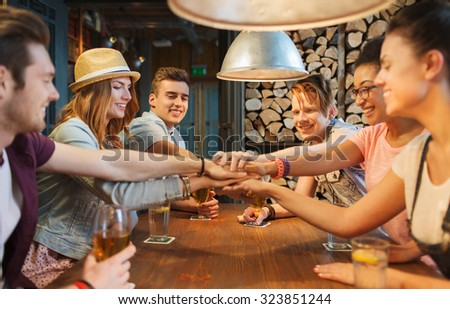 people, leisure, friendship and gesture concept - group of happy smiling friends with drinks putting hands on top of each other at bar or pub - stock photo