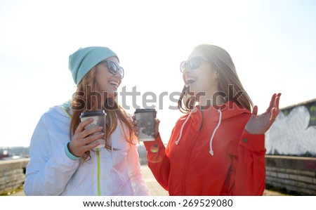 people, leisure, friendship, communication and takeaway drinks concept - happy teenage girls with coffee cups on city street - stock photo