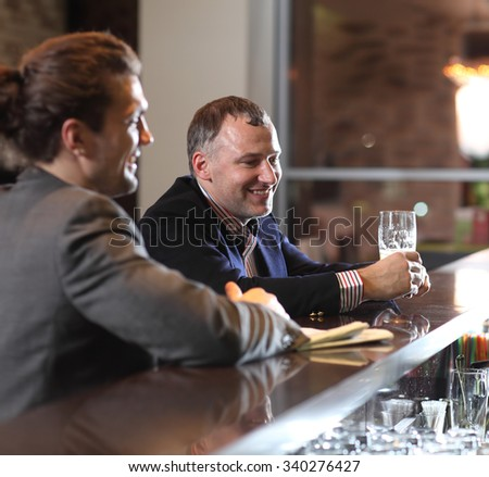People, leisure, friendship, communication  - happy male friends drinking beer and talking at bar