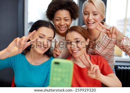 people, leisure, friendship, gesture and technology concept - happy young women taking selfie with smartphone and showing victory gesture - stock photo