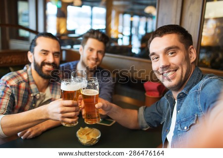 people, leisure, friendship, technology and bachelor party concept - happy male friends taking selfie and drinking beer at bar or pub - stock photo