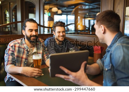 people, leisure, friendship, technology and bachelor party concept - happy male friends with tablet pc computer drinking beer at bar or pub - stock photo